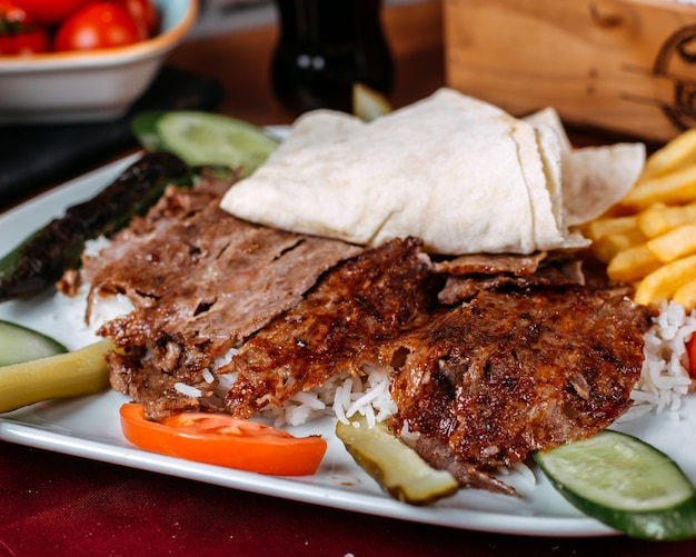 Close up of turkish kebab meat with rice french fries and fresh vegetables on a plate