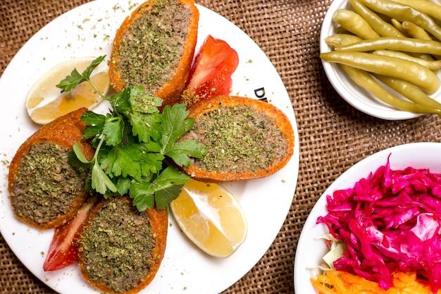 Primo piano di polpette di carne ripiene turche ichli kofte servito con pomodoro limone e prezzemolo