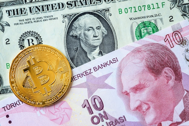 Close-up turkish ten lira and us one dollar banknotes and one golden bitcoin coin