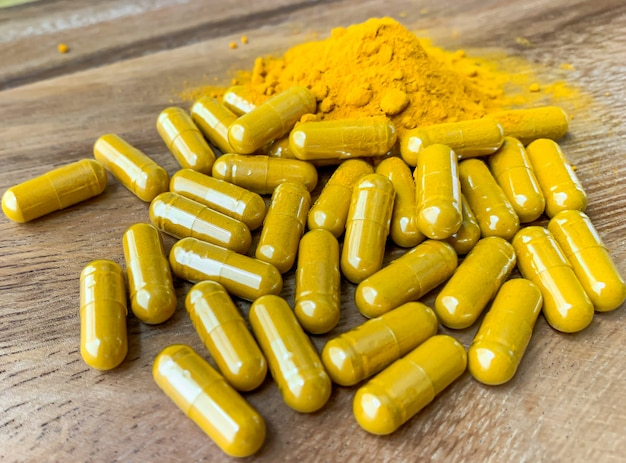 Close up turmeric or curcumin capsules and powder are on a brown wood table.