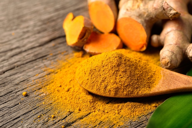 Close-up turmeric (curcumin) powder in wooden spoon with fresh rhizome on wood background.