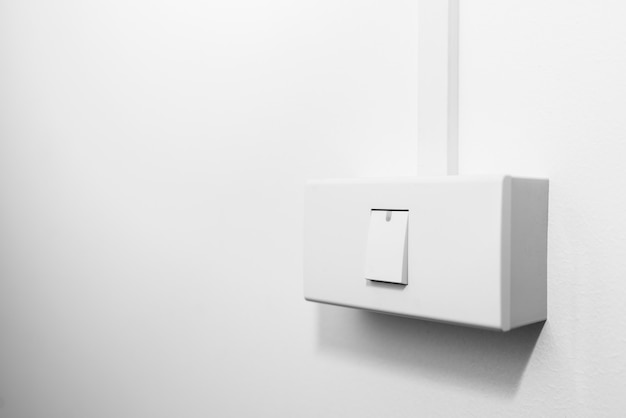Close up turning on or off on light switch with white cement or concrete wall