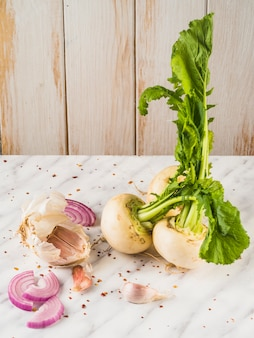 Close-up of turnip; onion slice and garlic cloves on marble surface