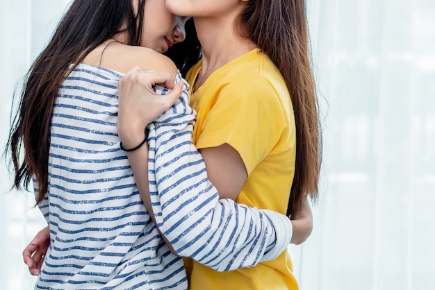 Close up of two asian lesbian women embracing in bedroom