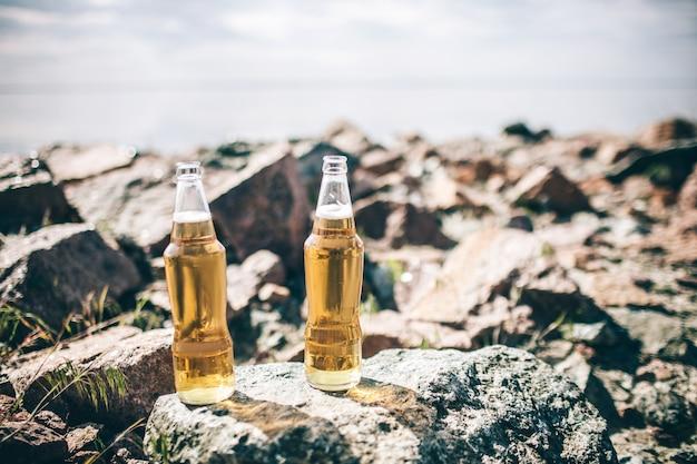 クローズアップ2本のビール瓶が空を背景に日差しの中で水の近くの石の上に立っています。