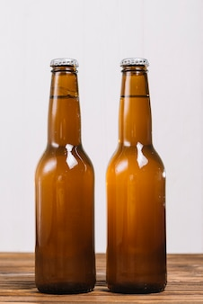 Close-up of two beer bottles on wooden surface