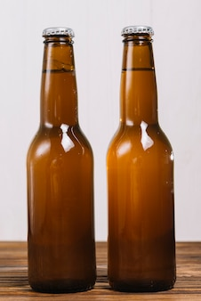 Close-up of two beer bottles on wooden table top