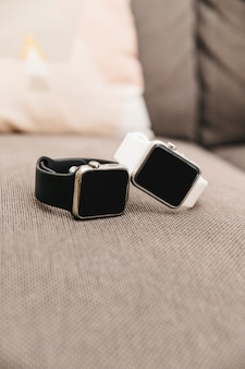 Close-up of two black and white smartwatch