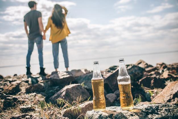 クローズアップ2本のビールがカップルの背景に太陽の下で水の近くの石の上に立っています。男と女は手をつないでいます。
