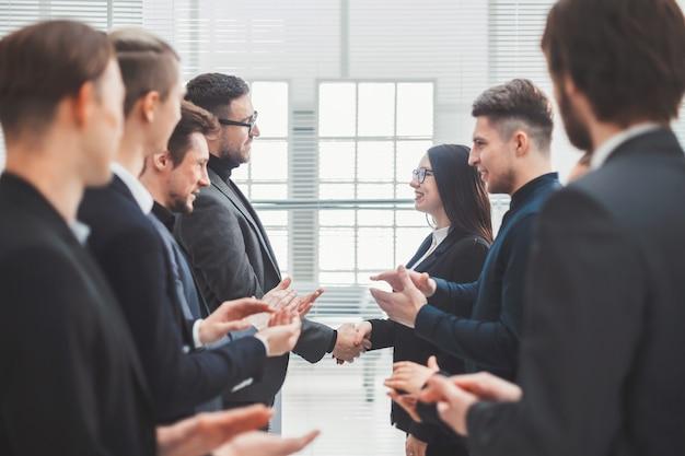 閉じる。リーダーを称賛する2つのビジネスチーム。会議とパートナーシップ