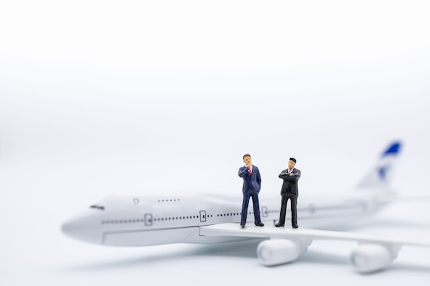 Close up of two businessman miniature figure standing on airplane wing on white.