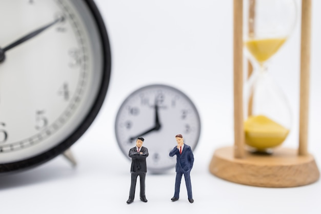 Close up of two businessman miniature figure standing with vintage alarm clock and sandglass.