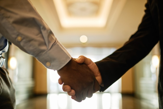 Close up of two businessmen shaking hands in office building hall, copy space