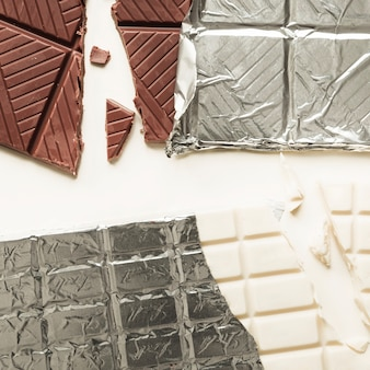 Close-up of two chocolate bars in silver foil on white background