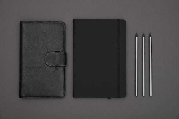 회색 종이 배경 위에 두 개의 닫힌 검은 가죽 커버 노트와 연필을 닫습니다.