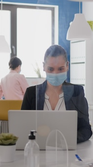 Close up of two coworkers talking about marketing project wearing protective medical face mask sitti...