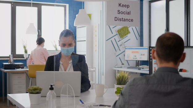 Close up of two coworkers talking about marketing project wearing protective medical face mask sitting in new normal office during coronavirus global pandemic. team mantain social distancing