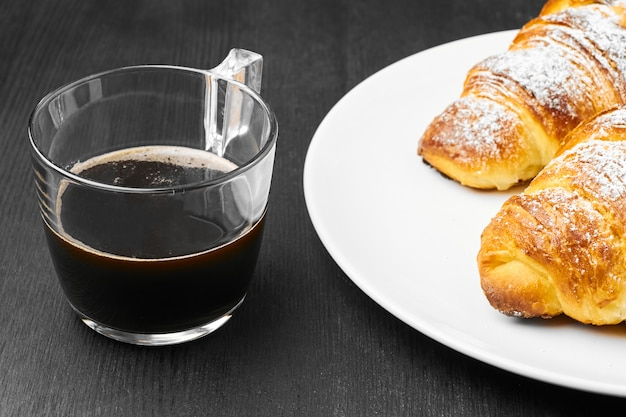 Close up two croissants on a white plate and a cup of coffee on a black wall. concept of italian breakfast.