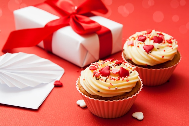Close-up of two cupcakes with cream and heart decor on a red surface with gift and envelope.