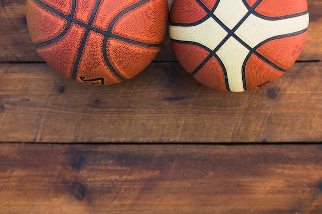 Close-up of two different type of basketball on wooden table