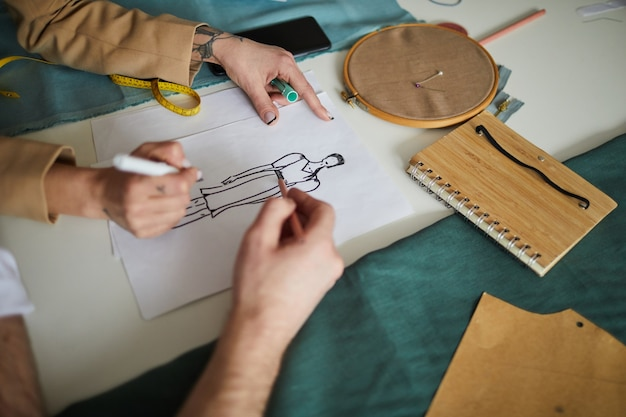 Close-up of two fashion designers drawing sketch of new dress with pencils together