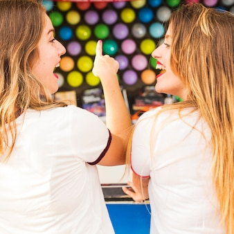 Close-up of two female friends enjoying game in amusement park