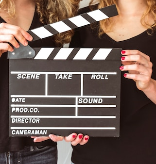 Close-up of two female friends holding clapper board