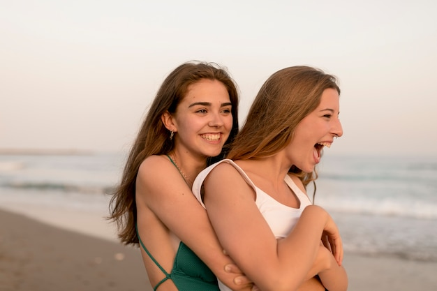 Close-up of two female friends hugging from behind at beach