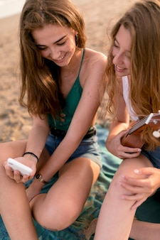 Close-up of two female friends looking at mobile phone
