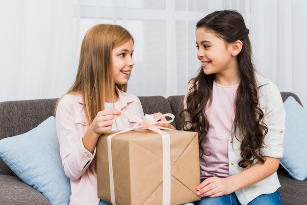 Close-up of two female friends sitting on sofa looking at each other while opening the gift box