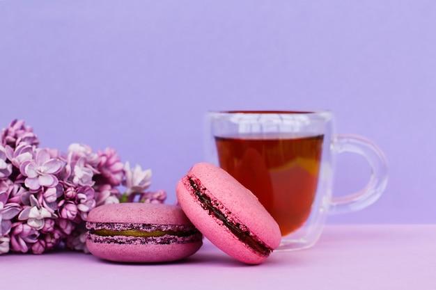 紫の背景に2つのフランスのカラフルなケーキマカロン、ティーカップ、ライラックの花をクローズアップ