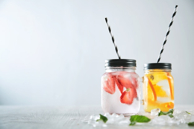 Close up two fresh homemade lemonades made from sparkling water, ice, strawberry and orange. melted crashed ice and mint leaves around, striped drinking straw inside rustic jars.