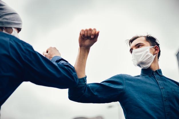 閉じる。街の通りでひじを使って挨拶する2人の友人。健康保護の概念