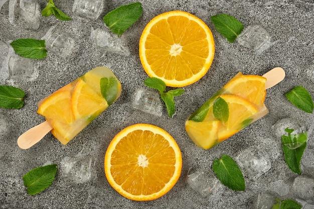 신선한 오렌지 조각, 녹색 민트 잎, 얼음 조각으로 두 개의 과일 아이스크림 아이스 캔디를 닫습니다