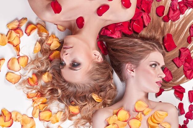 Закройте вверх. две подруги, лежа в салоне спа среди лепестков роз. концепция здорового образа жизни