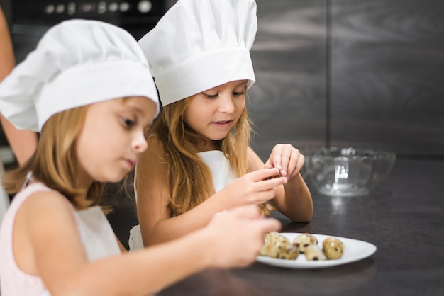 Close-up of two girls in chef hat peeling quail eggs in plate at home