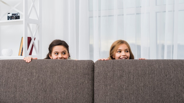 Close-up of two girls hiding behind the grey sofa looking at camera