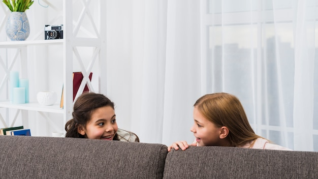 Close-up of two girls hiding behind the sofa looking at each other at home