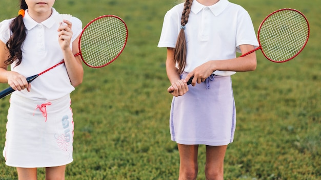 Close-up of two girls holding badminton in hand
