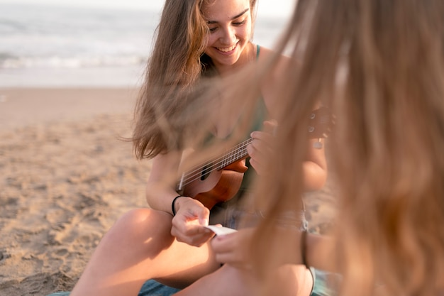 Close-up of two girls sitting on beach looking at photo