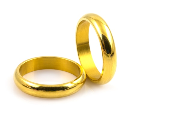 Close up of two gold rings for wedding isolated on white background
