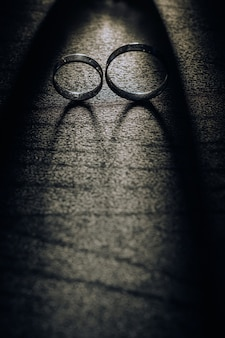Close-up of two gold wedding rings on a black background