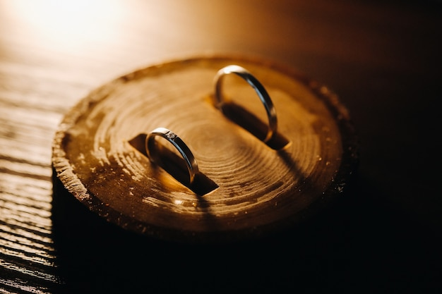 Close-up of two gold wedding rings lying on a wooden board.wedding ring.wedding ring.