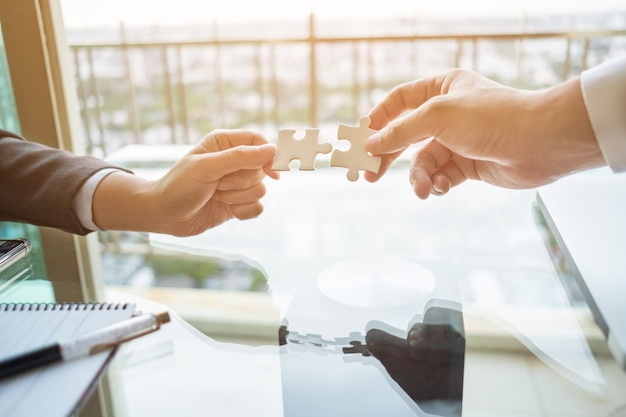 Close up two hands connect two jigsaw puzzle. business, success and strategy concept.