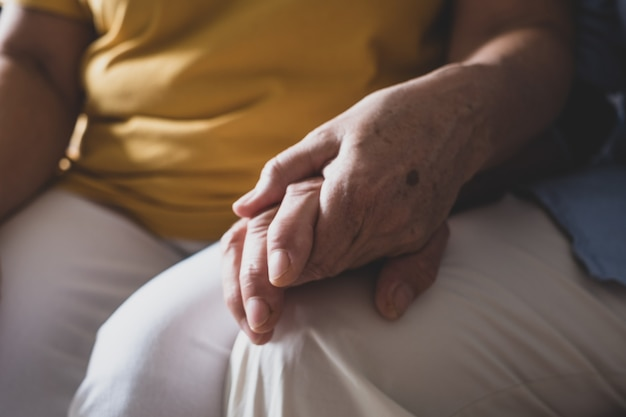 Close up of two hands holding each other together at home taking care - senior and mature people hands