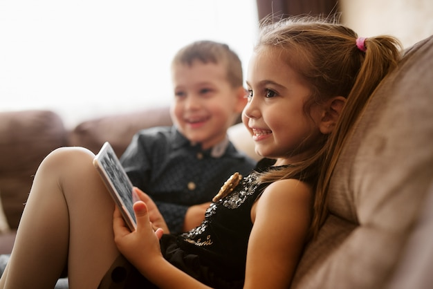 Close up of two happy adorable little toddler children sitting on the sofa and smiling to their parents.