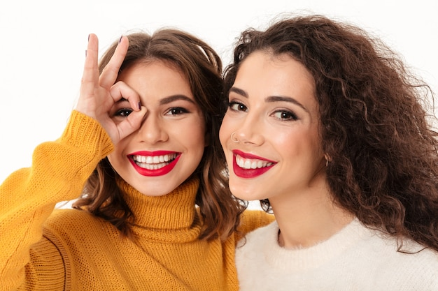 Close up two happy girls in sweaters having fun  over white wall