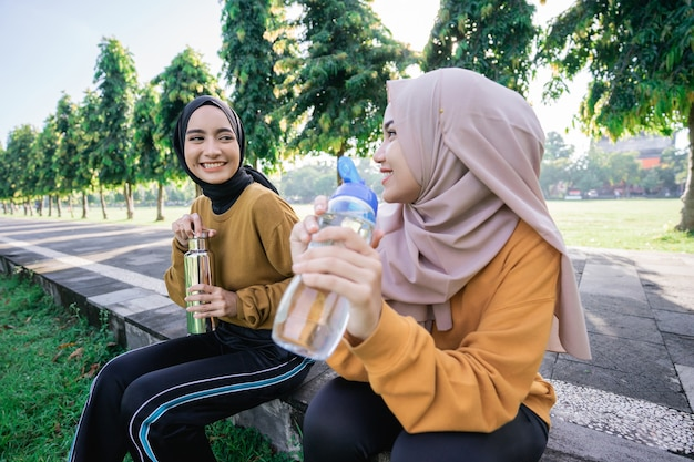 Close up of two happy muslim girls after sports together in the afternoon when breaking the fast and drinking water using bottles in the park