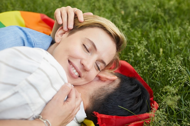 Close-up of two happy women lying on green grass and embracing they love each other