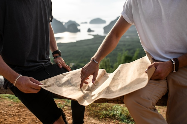 Close up two hipster friends travelers looking at the paper map to find correct way